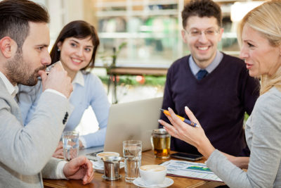 Group of business people with laptop meeting in coffee shop
